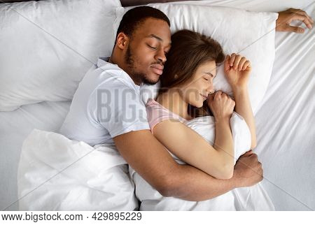 Top View Of Loving Interracial Couple Sleeping In Bed, Hugging Each Other. Diverse Love And Relation