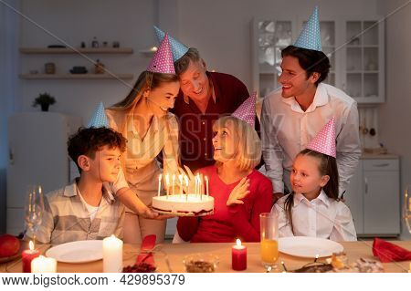Happy Extended Multi Generation Family Having Birthday Party, Giving Senior Woman B-day Cake With Ca