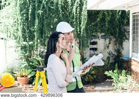 Asian Attractive Woman And Male Engineer, Are Looking At Point And Discuss About Renovating The Old