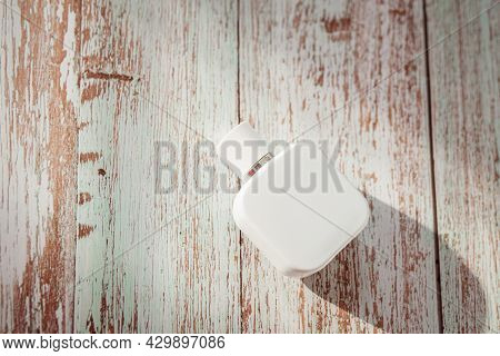 White Perfume Bottle On Wooden Textured Background. Summer Scent Concept For Vacation