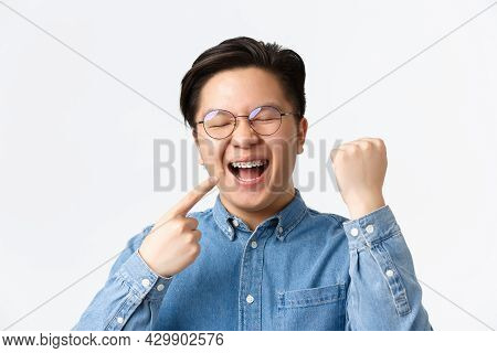 Orthodontics And Stomatology Concept. Close-up Of Satisfied Happy Asian Man Pointing At His Dental B