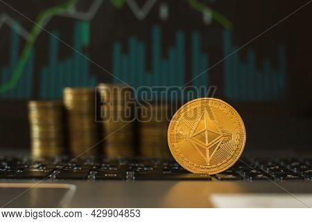 The Ethereum Coin Against The Background Of Stacks Of Coins And A Financial Chart. Digital Currency.