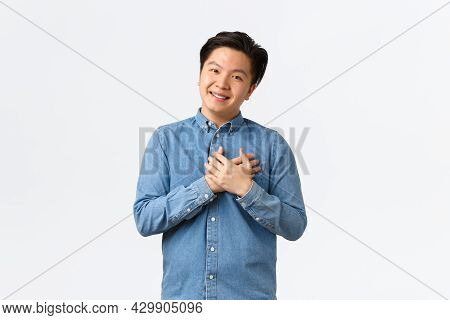 Hopeful And Glad Young Asian Male Entrepreneur Starting Own Startup, Holding Hands On Heart As Grate
