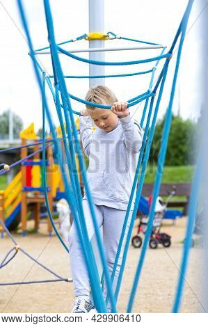 Little Girl Climbing In An Adventure Park. The Girl Loves To Climb In The Adventure Of The Rope Cour