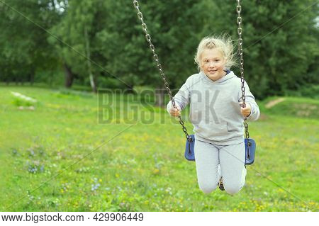 Little Girl In A Gray T-shirt On A Swing On A Summer Day. Girl Riding On A Swing