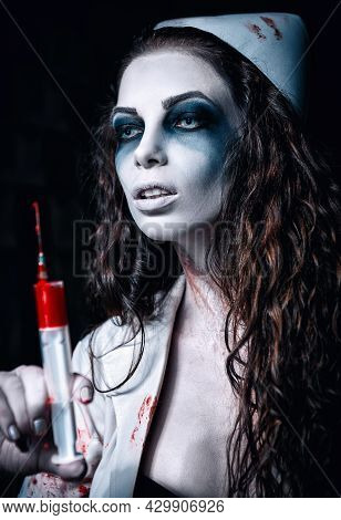 Horror Shot: The Scary Wicked Mad Nurse (doctor) With Bloody Syringe In Hand. Zombie Woman (living D