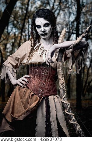 Halloween Theme: Ugly Grim Voodoo Witch With Staff. Portrait Of The Evil Sorceress In Dark Forest. Z