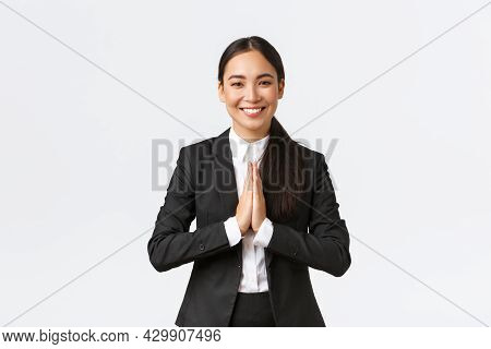Hopeful Glad Asian Businesswoman In Black Suit Bowing Politely And Say Namaste, Greeting Clients And