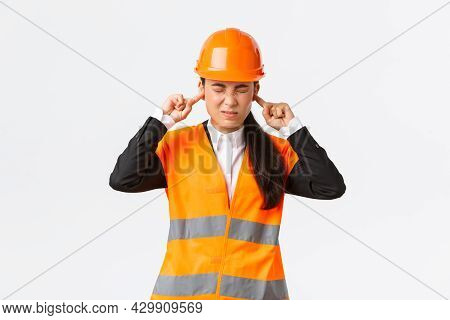 Asian Female Company Manager Feeling Discomfort, Chief Engineer Shut Ears And Grimacing From Annoyin
