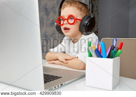 Cute Child In Red Glasses And Headphones Has Fun Communicating Online Via Video Link Using A Laptop.