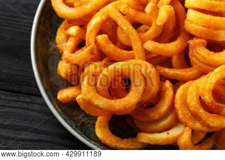 Golden Seasoned Curly Fries On Rustic Plate. Ready To Eat