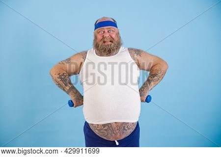 Happy Plump Man With Small Dumbbells Holds Hands On Waist On Light Blue Background