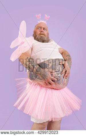 Surprised Plump Male Person In Fairy Costume Holds Large Tummy On Purple Background