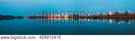Panoramic View Of Urban Residential Area Overlooks To City Lake Or River And Park In Evening Illumin