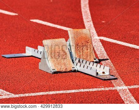 Side View Of Worn Out Starting Blocks On Running Tracks. Red Running Tracks Lanes At Track And Field
