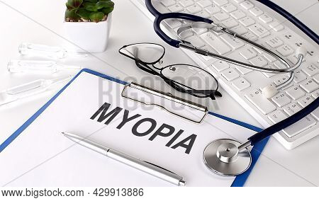 Myopia Text On White Paper On The White Background. Stethoscope ,glasses And Keyboard