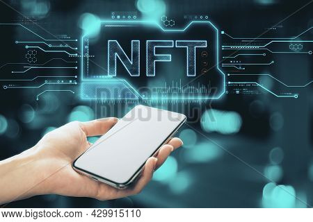 Close Up Of Hand Holding Empty White Smartphone With Glowing Nft Chip Hologram On Blurry Bokeh Backg