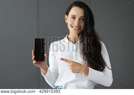 Young Woman Holding Mobile Phone And Pointing At It With Forefinger