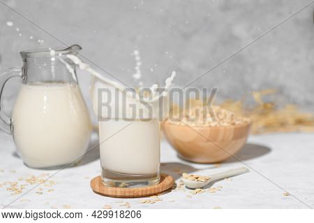 Splash Of Oat Milk In A Glass And Jug On A Grey Stone Table Background And A Bowl With Oat Flake. Ju