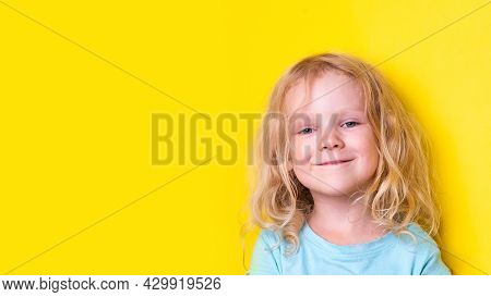 Portrait Beautiful Curly Funny Little Girl With Blond Curly Hair Wearing Blue T-shirt On Yellow Back