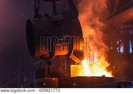 Molten Metal Is Poured With Sparks From Ladle Into Mold. Smelting Of Multi-ton Cast Iron Parts In Fo