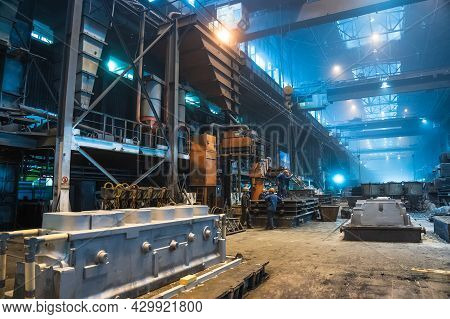 Interior Of Steel Mill. Workers In Workshop Of Metallurgical Plant. Foundry And Heavy Industry Build