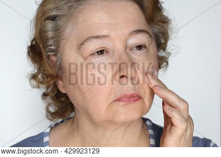 Elderly Woman Cares For Her Face Applies Anti-aging Cream To Her Face