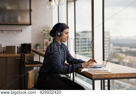 Indian Businesswoman Wear Headphones Use Laptop Communicating By Videocall