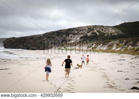 Children Running Along Beach Towards Large Rocky Cliff At Portland, Victoria Australia