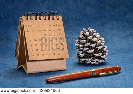 December 2021 - spiral desktop calendar against handmade, textured paper with a frosty pine cone, time, business and winter holiday concept