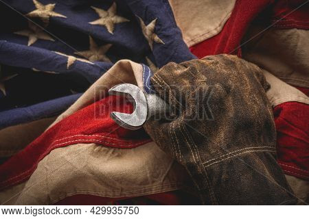 Worn work glove holding old wrench and US American flag. Made in USA, American workforce, blue collar worker, or Labor Day concept.
