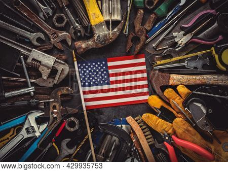Patriotic collection of worn and used work tools with small US American flag. Made in USA, American workforce, or Labor Day concept.
