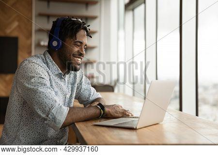 African Guy Wear Headphones Use Laptop Enjoy Conversation On Videocall