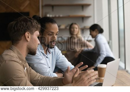 Multiethnic Colleagues Sit In Coworking Space Use Laptop Discuss Task