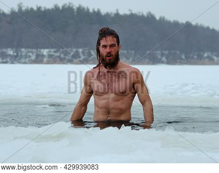 Fit Man Standing In Ice Hole Against Winter Landscape