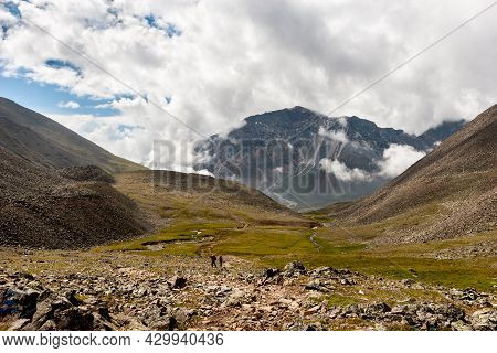 Mountain Valley With A Passage Between The Mountains And A Large Mountain At The End. Low Clouds Ove
