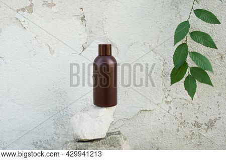 Bottle Of Shampoo And Conditioner Of Cosmetics Over Wahite Wall Background With Green Leaves, Essent