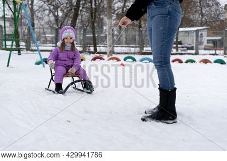 A Woman Is Carrying A Child On A Sled. Mom Walks With Her Daughter Along A Snowy Path. Merry Winter