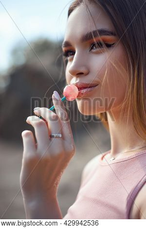 Beautiful Woman Licking A Lollipop Close-up. Red Shadows On The Eyes Of A Girl, Professional Makeup,