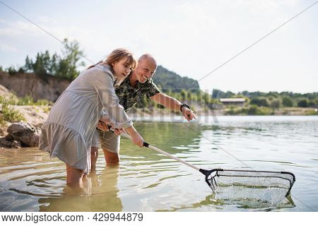 Happy Preteen Girl And Grandfather With Fishing Net On Summer Holiday By Lake.