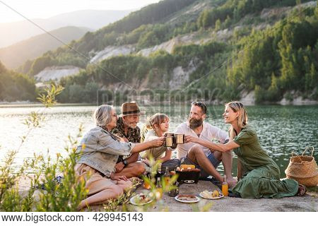 Happy Multigeneration Family On Summer Holiday Trip, Barbecue By Lake.