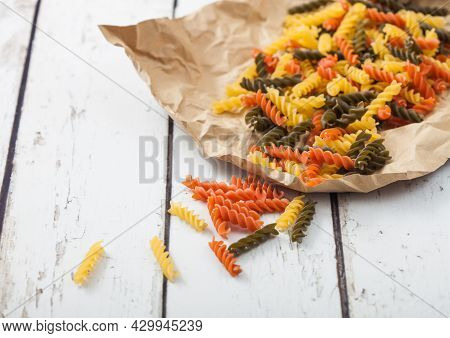 Raw Homemade Tricolore Fusilli Pasta In Brown Paper On White Wooden Table Background.