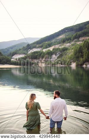 Rear View Of Mature Couple In Love Standing In Nature, Holding Hands.