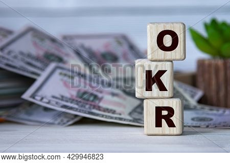 Okr (objectives And Key Results) - Acronym On Wooden Cubes On The Background Of A Cactus And Banknot