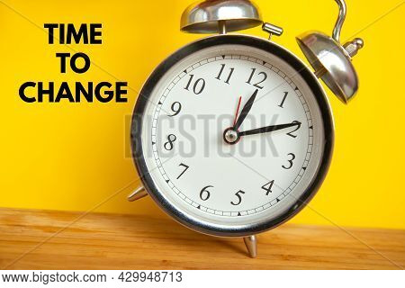Retro Alarm Clock On Bright Yellow Background With An Inscription Time To Change. Time Concept