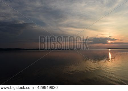 Sunbeam From Clouds At Sunset Over Calm Lake Water