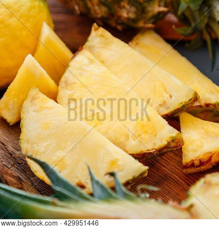 Sliced Pineapple On Cutting Board. Summer Fruit Sliced Pineapple Slicing Process In Kitchen On Dark