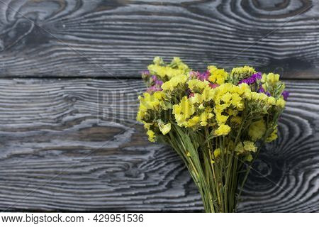 Statice Bouquet Of Flowers Of Different Colors. Against The Background Of Pine Boards.