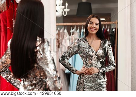 Woman Trying On Dress In Clothing Rental Salon