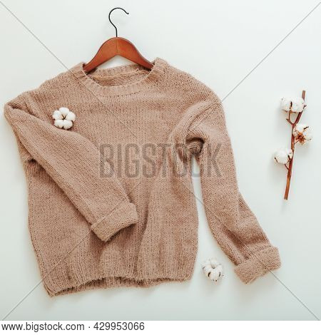 Knitted Beige Sweater On Hanger With Cotton Flowers. Cotton Sweater Flies Flat Lay Twig Cotton On Wh